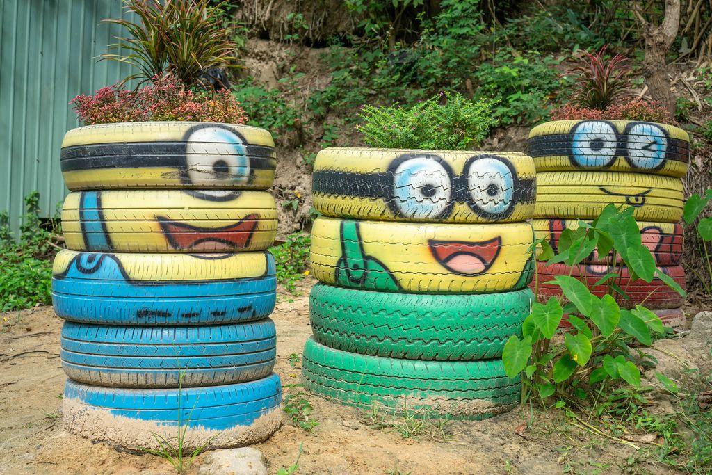 Alte, gestapelte Reifen kunstvoll als Minions bemalt und mit Blumen bepflanzt in Mui Ne, Vietnam