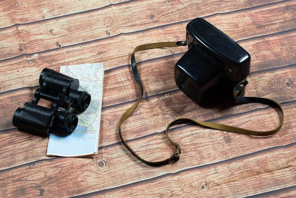 Alte Kamera und Fernglas mit Landkarte auf dem Holzboden