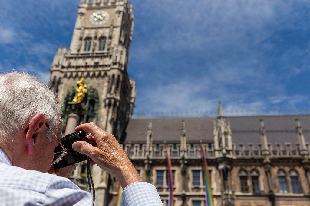 Alter Mann fotografiert bunte Regenbogenfahnen vor dem Neuen Rathaus während des Christoper Street Day Festivalwochenendes in München