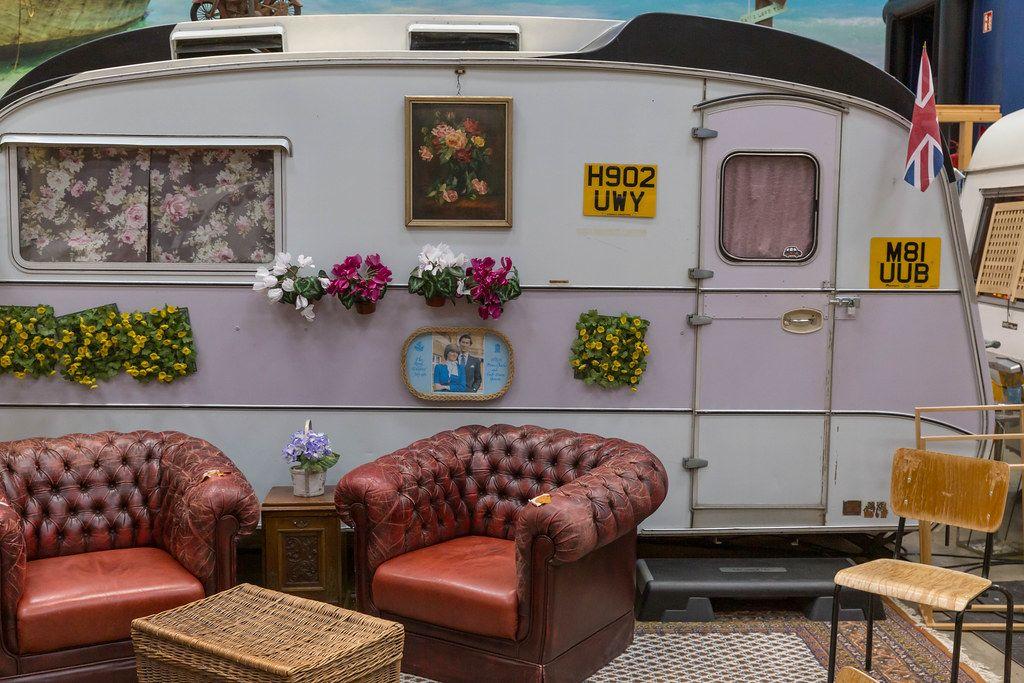 Alter Wohnwagen mit Blumen & Bildern von Lady Di und Prinz Charles als Hostelzimmer mit Wohnzimmerflair & Vintagesessel aus rotem Leder