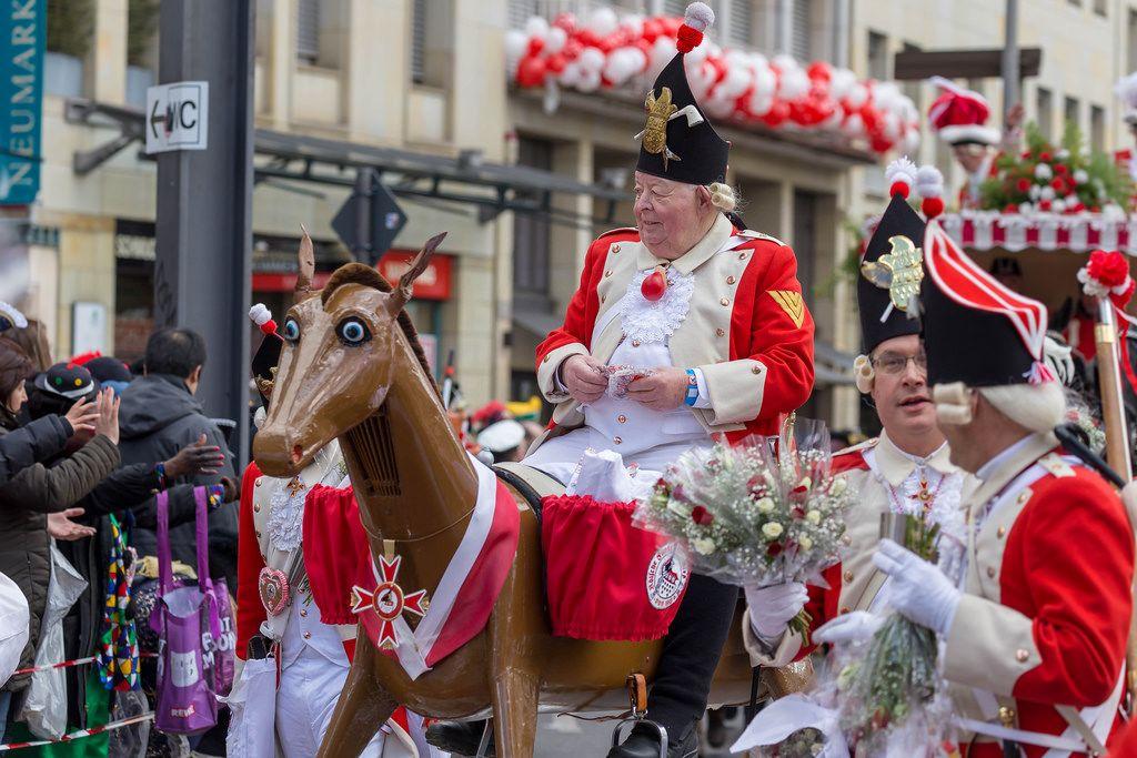 Älteres Mitglied der Roten Funken auf einer Pferdeattrappe - Kölner Karneval 2018