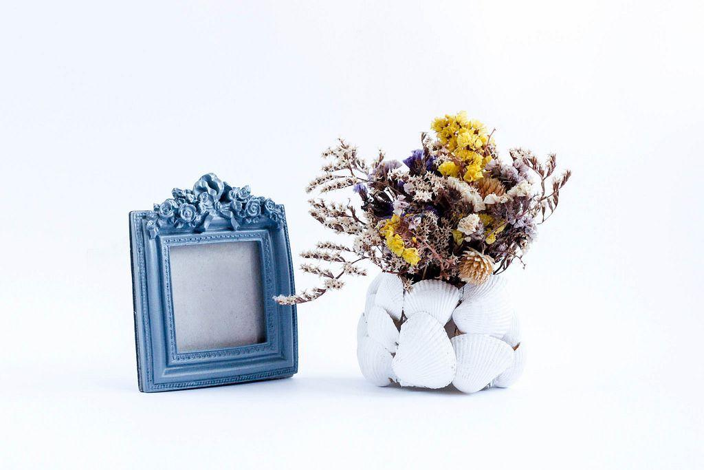 Altmodischer Fotorahmen und eine Vase mit ausgetrockneten Blumen