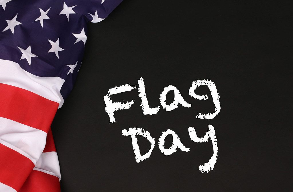 American flag with the text Flag day against a blackboard background