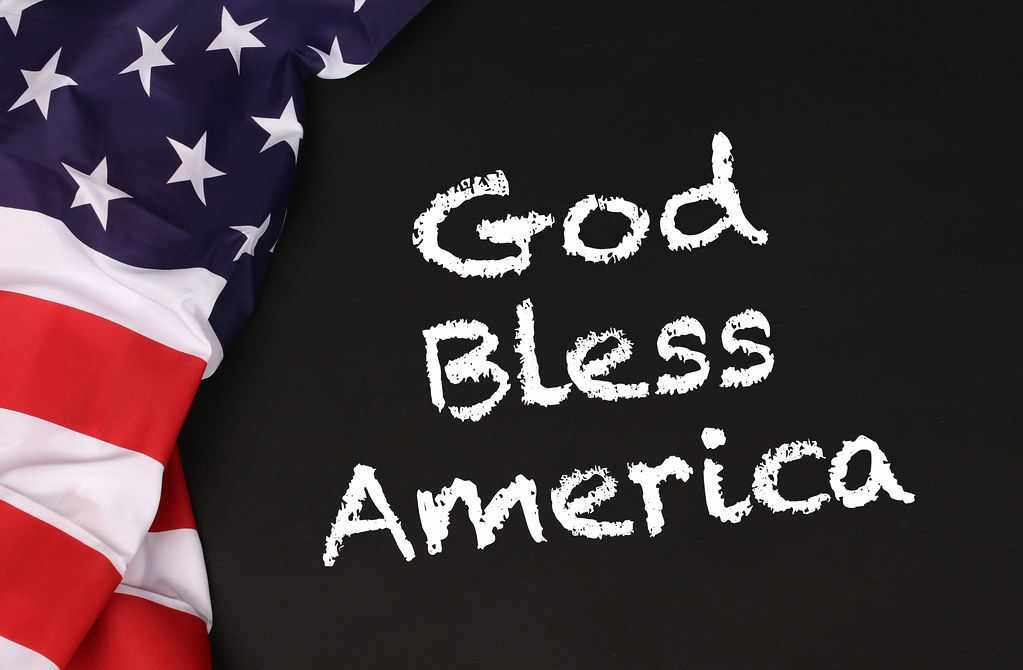 American flag with the text God Bless America against a blackboard background