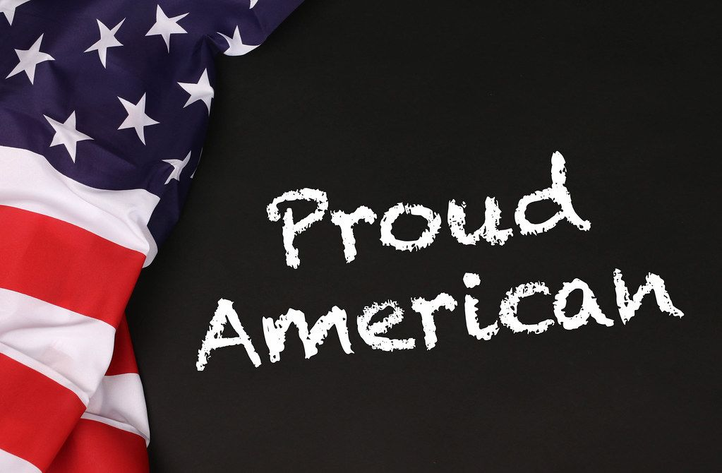 American flag with the text Proud American against a blackboard background