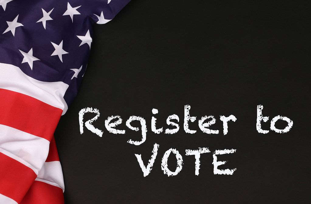American flag with the text Register to Vote against a blackboard background.jpg