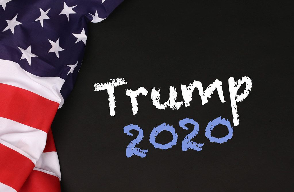 American flag with the text Trump 2020 against a blackboard background