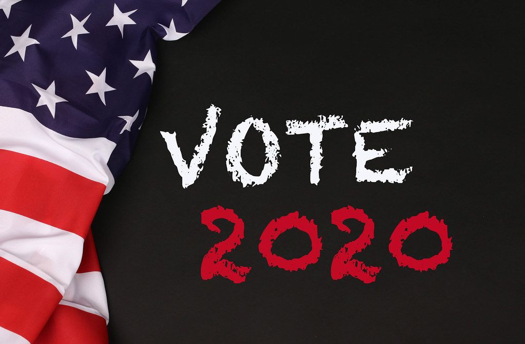 American flag with the text Vote 2020 against a blackboard background