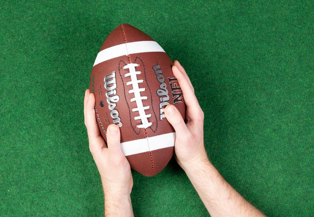 American football player holding up football ball