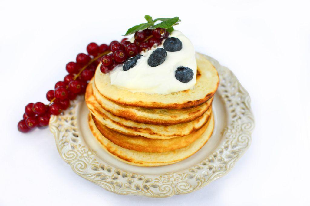 Amerikanische Pancakes mit Sahne, Blaubeeren und roten Johannisbeeren