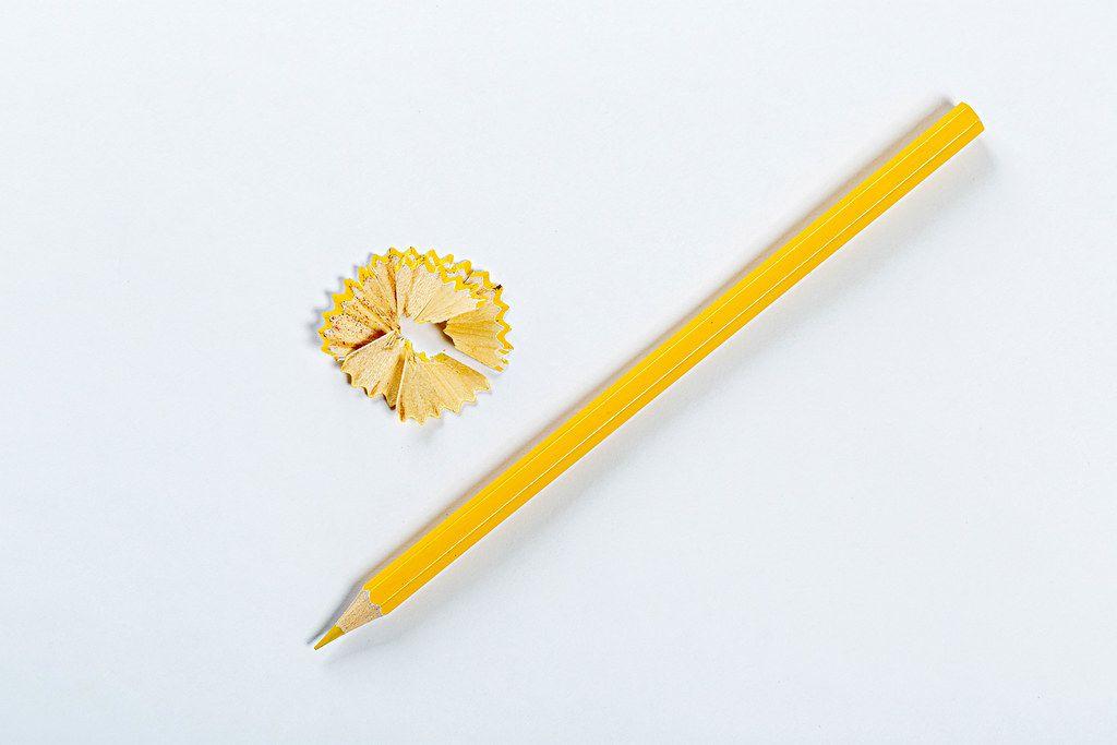 Angespitzter gelber Buntstift auf weißer Oberfläche