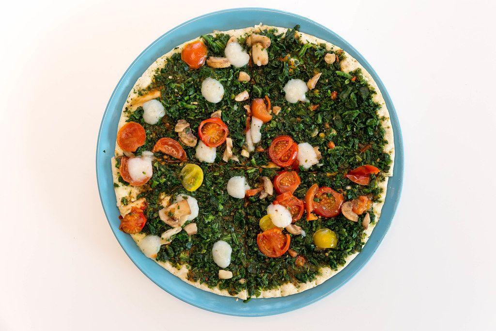 Ansicht von oben auf die Fleischersatz-Pizza Verdura der Trattoria Alfredo, in vier Stücke geteilt und mit veganem Belege wie Spinat, Pilzen und Tomaten
