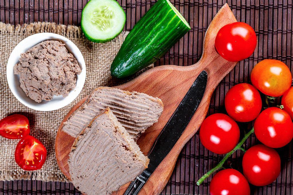 Ansicht von oben, auf ein geschmiertes Brot mit Leberwurst auf einem Frühstücksbrettchen, neben frischem Gemüse