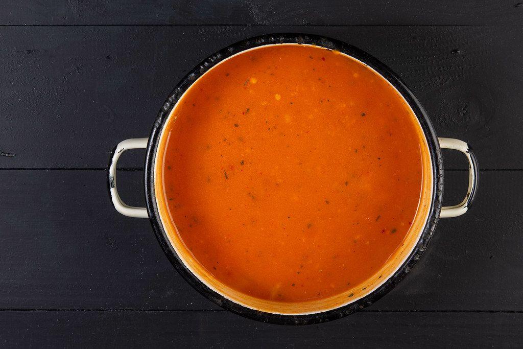 Ansicht von oben auf eine Tomatensoße in einem alten, rustikalen Vintage-Kochtopf