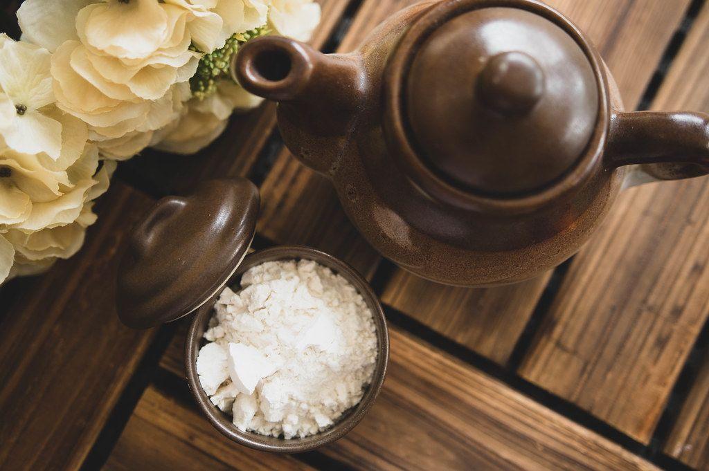 Ansicht von oben auf eine Zuckerdose mit weißem Pulver, neben einer braunen Teekanne aus Keramik