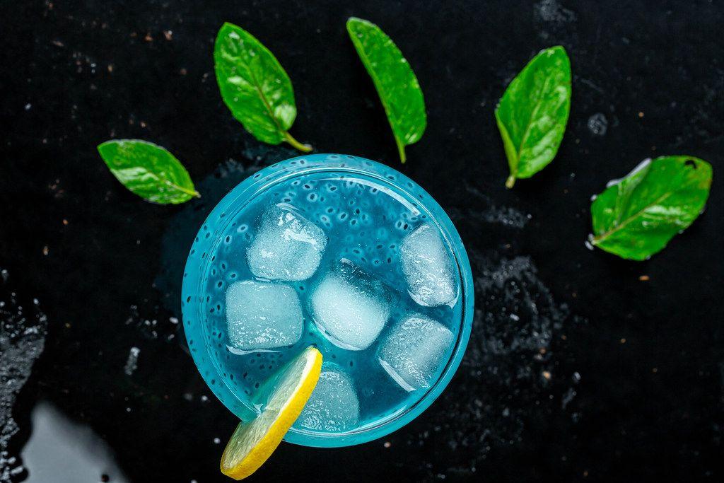 Ansicht von oben auf einen erfrischenden, blauen Cocktail mit Eiswürfeln, Zitronenscheibe und Minzblättern, auf einem schwarzen Tisch