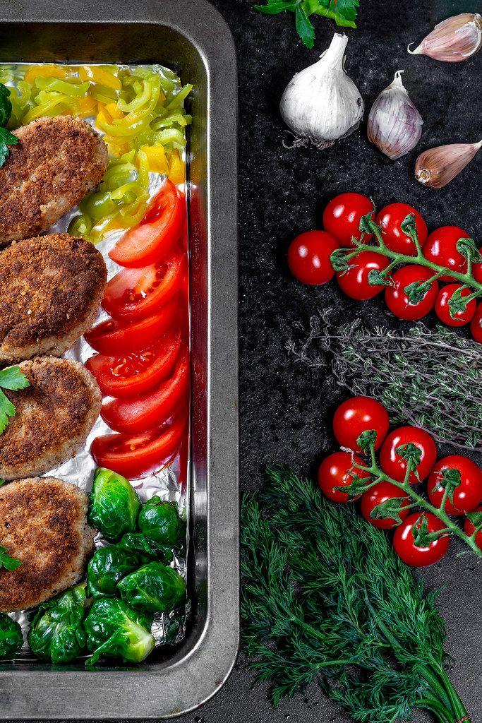 Ansicht von oben auf Fleischbuletten, neben geschnittenem Gemüse, Knoblauch und Kräutern, auf einem schwarzen Backblech