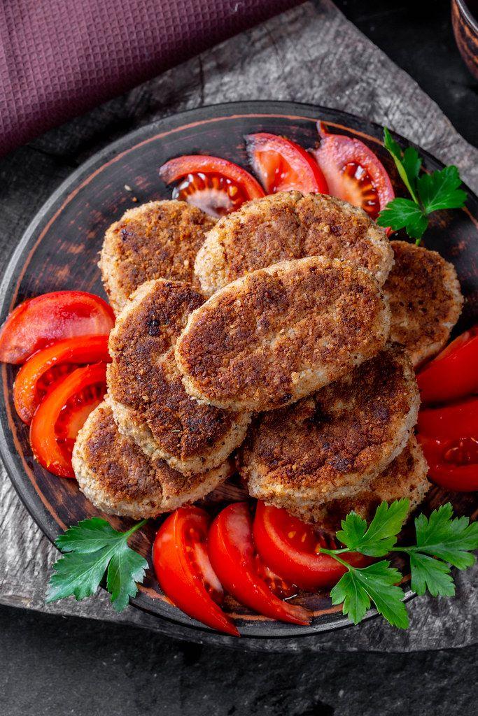Ansicht von oben auf frischgebratene, selbstgemachte Schnitzel, neben Tomaten und Kräutern