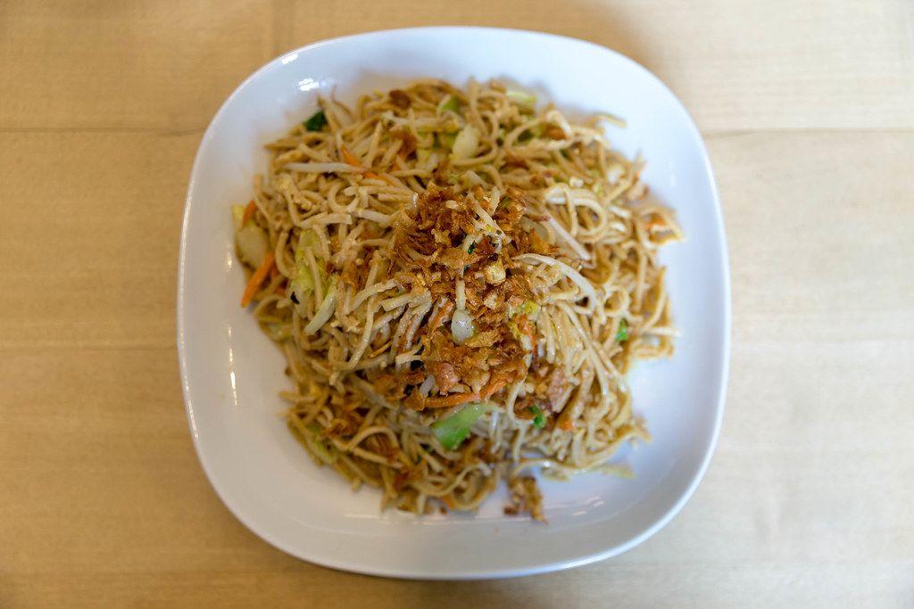Ansicht von oben auf gebratene Nudeln mit buntem Gemüse und Ei, auf einem weißen Teller auf einem Holztisch, als vegetarische Hauptspeise