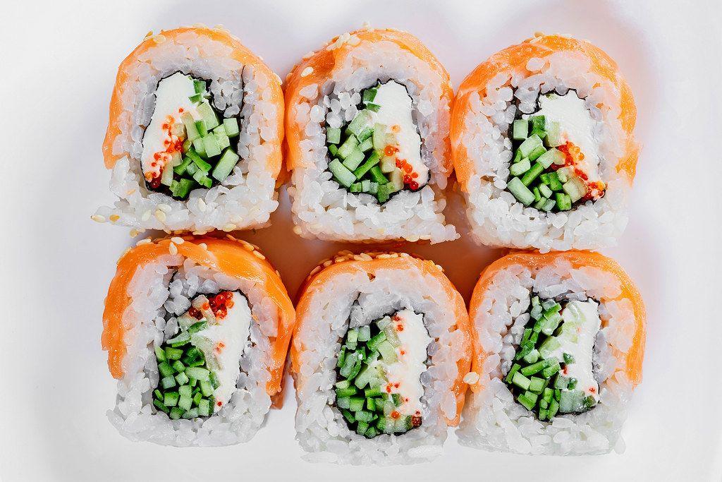 Ansicht von oben, auf geschnittene Sushi-Rollen Philadelphia auf einem weißen Untergrund