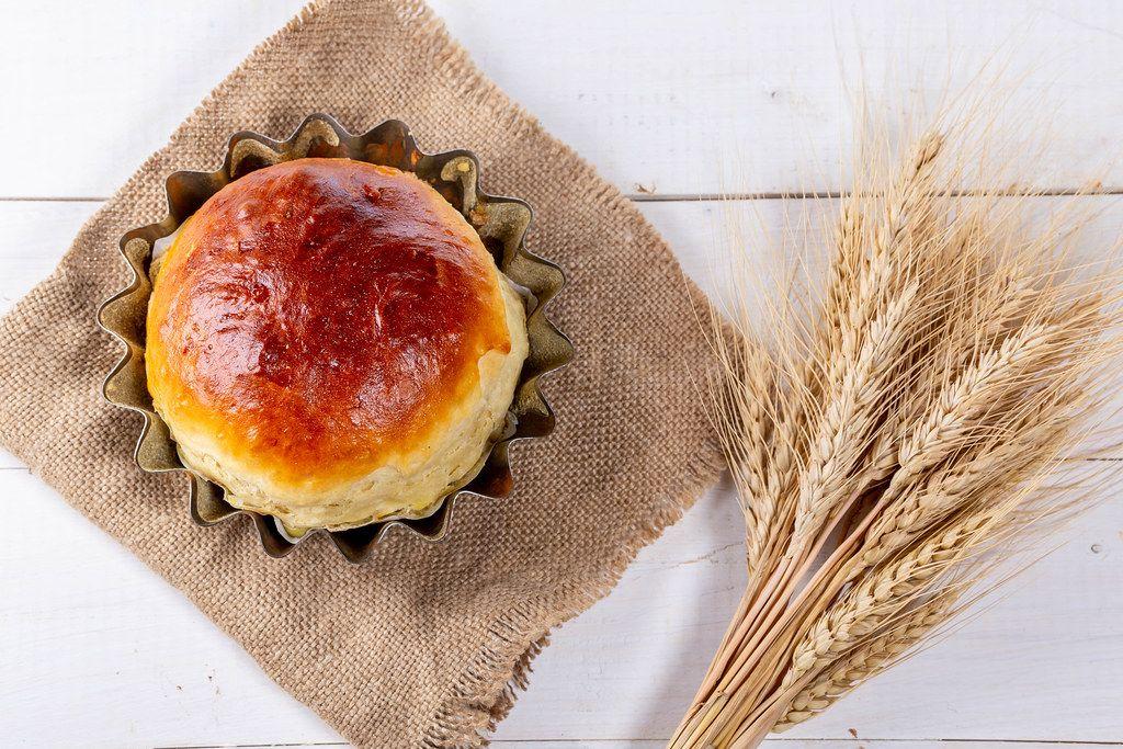 Ansicht von oben auf selbstgebackenes Frühstücks-Brot in der runden Backform, neben Ähren aus Weizen, auf einem Leinensack-Tuch