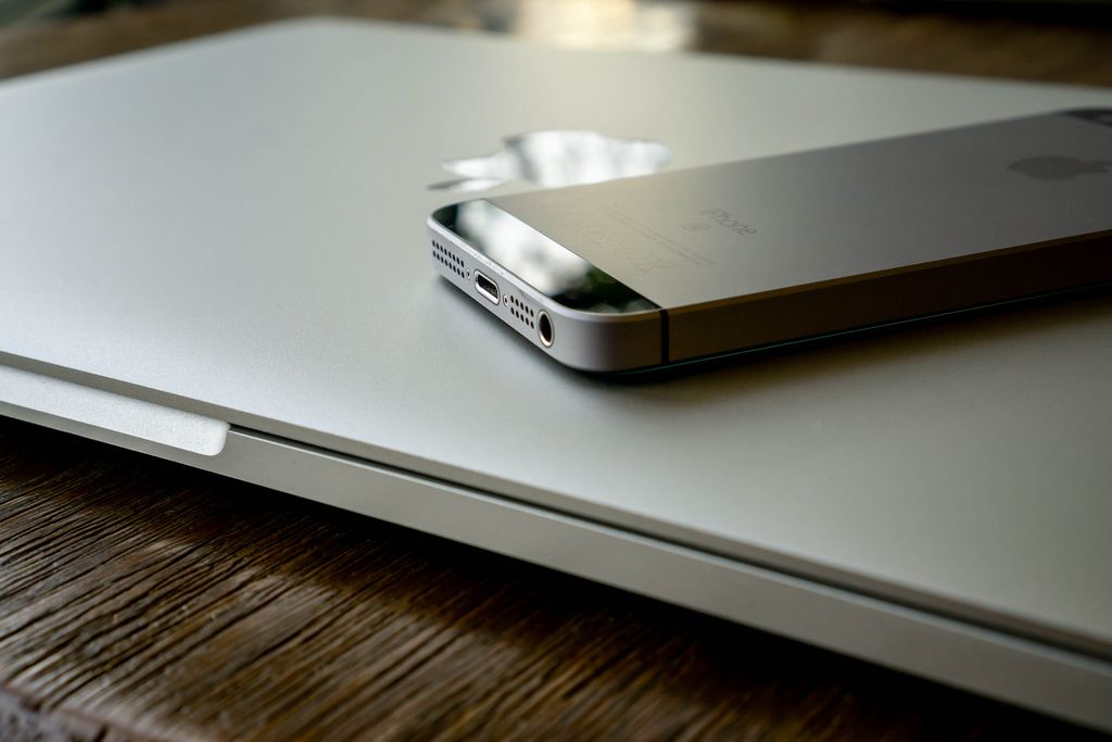 Apple iPhone and MacBook on a Wooden Table with Reflection
