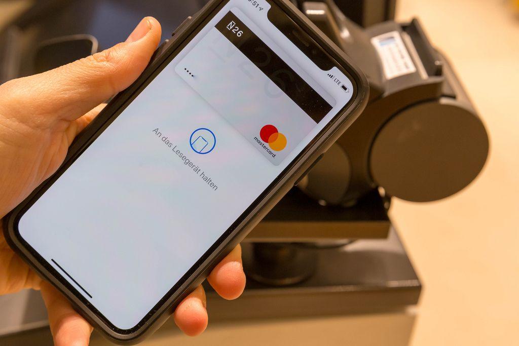 Apple Pay auf in der Hand gehaltenem Smartphone vor Kasse