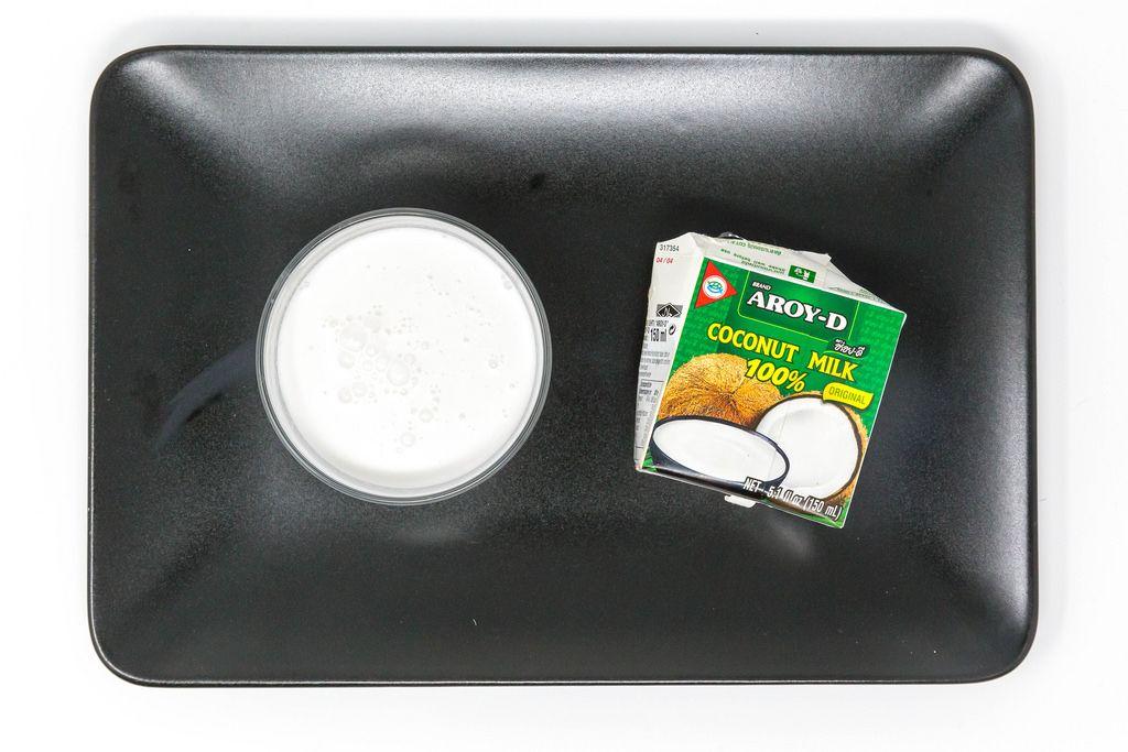 Aroy D - Kokosmilch von oben im Glas mit Verpackung - Aufsicht - Bildseite oben