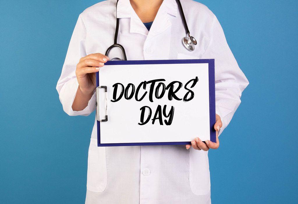 Arzt hält ein Schild mit der Schrift 'Doctor's Day' im blauen Hintergrund