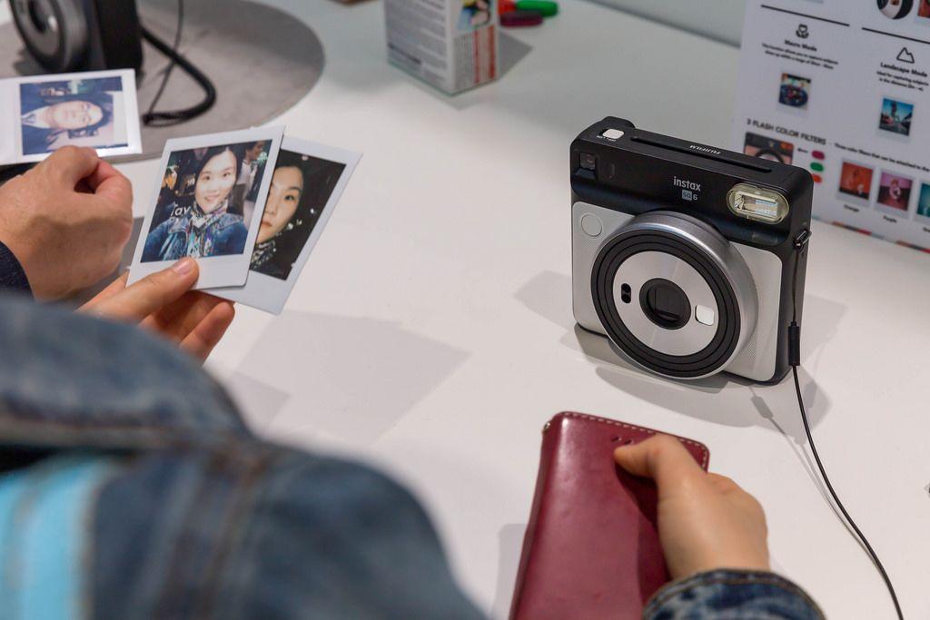 Asiatische Frau hält Ausdruck von Fotos der Sofortbildkamera Instax Square SQ6 an der Photokina in Köln