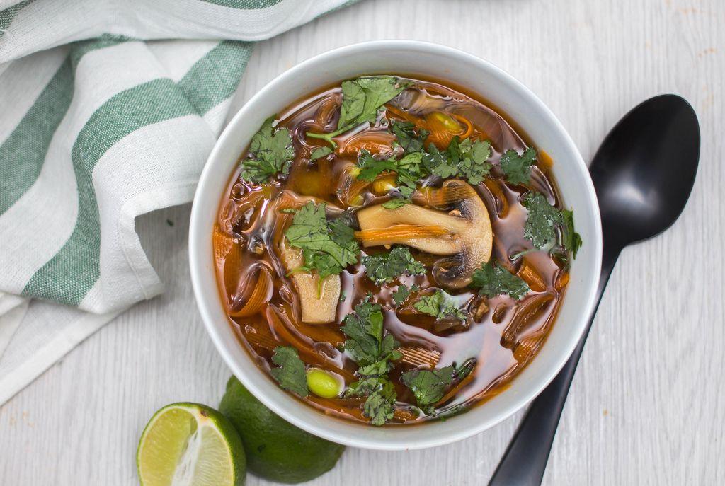 Asiatische Suppe mit verschiedenen Pilzen, Bambussprossen und Petersilie neben Limette