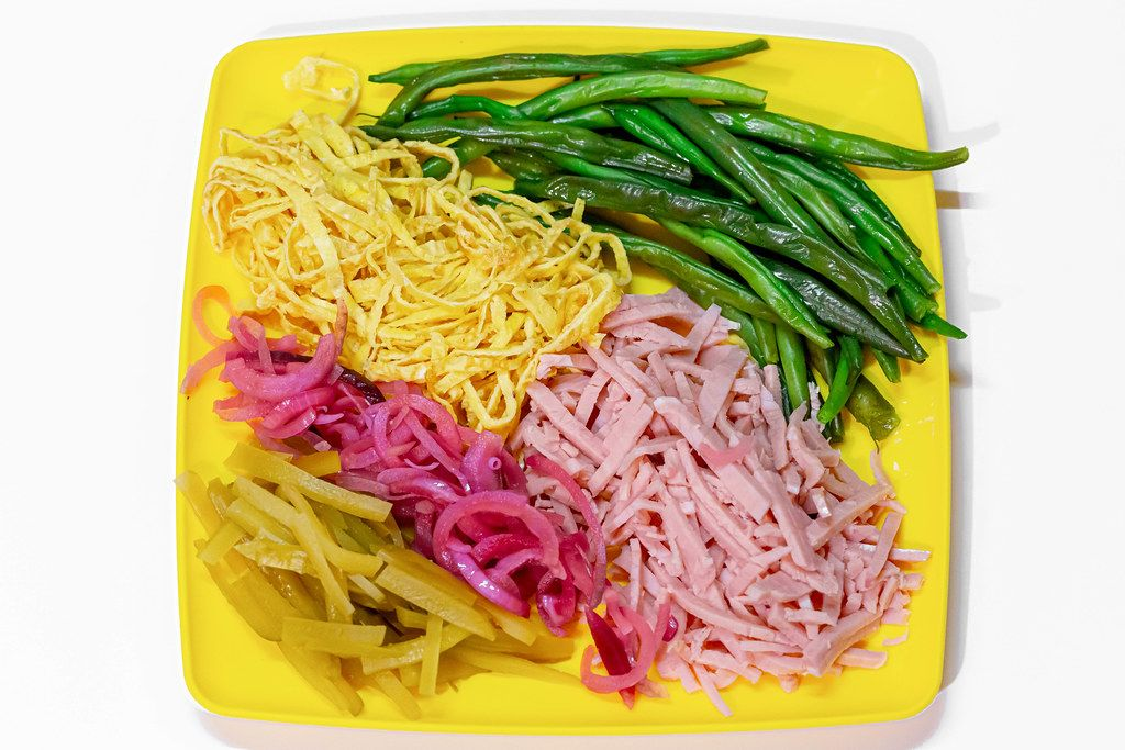 Asparagus beans, sliced ham and scrambled eggs, pickled purple onion and cucumbers on a yellow plate. Top view