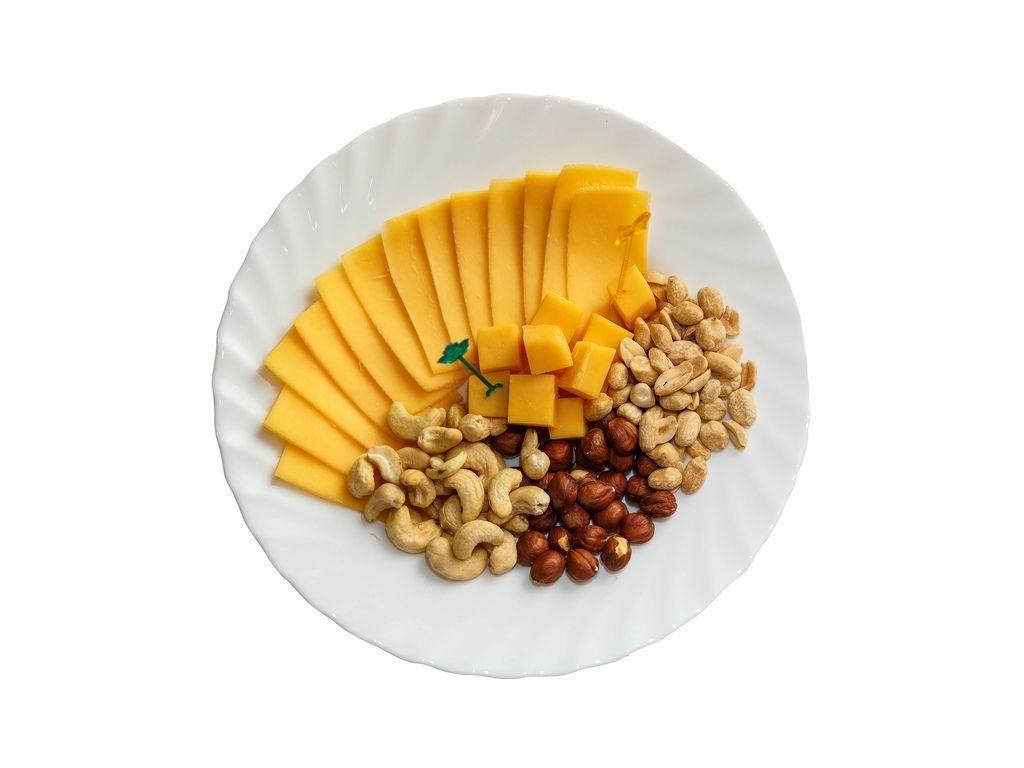 Assorted cheese and nuts in the plate on white background
