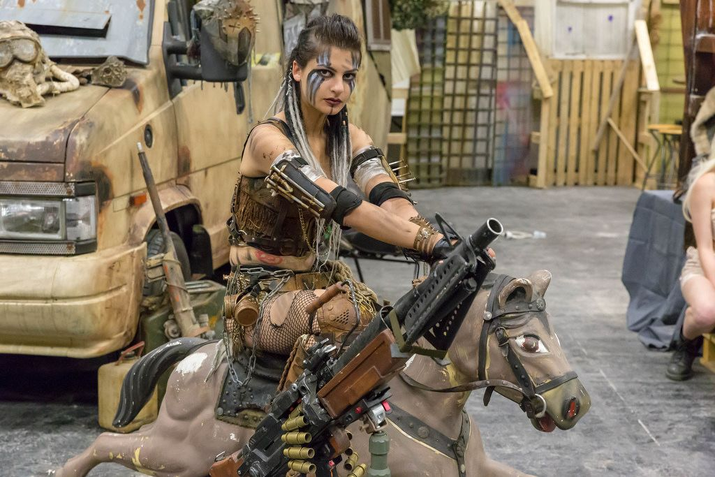 Attractive female cosplayer sitting on a merry go round horse