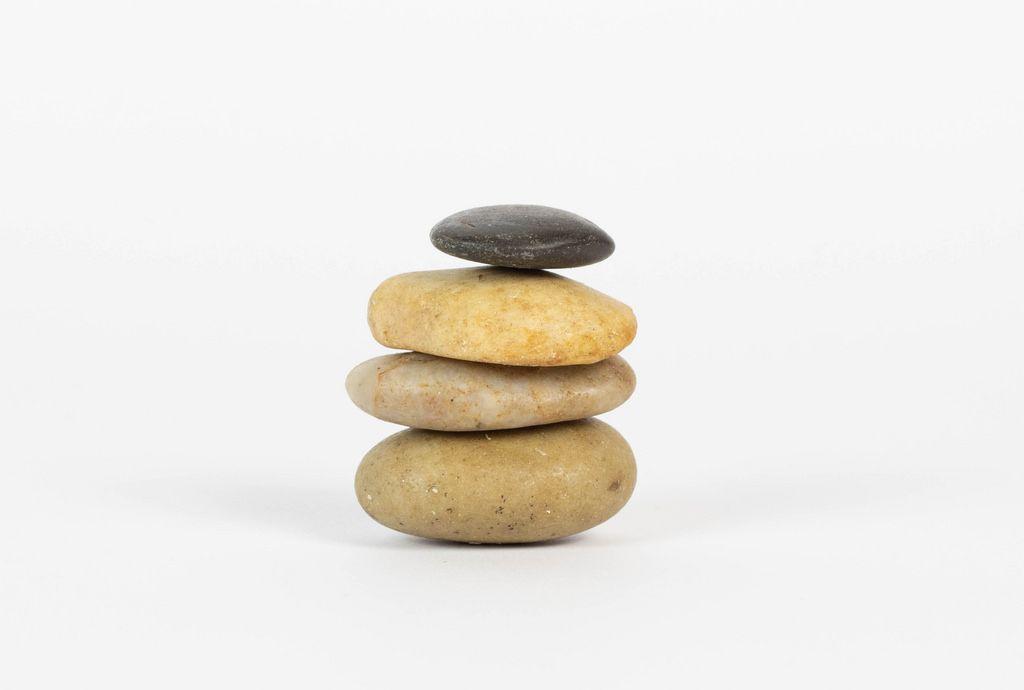 Aufeinander gestapelte Steine vor weißem Hintergrund