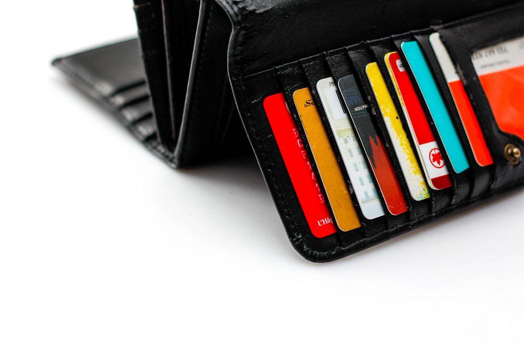 Aufgeschlagene Brieftasche mit Karten vor weißem Hintergrund