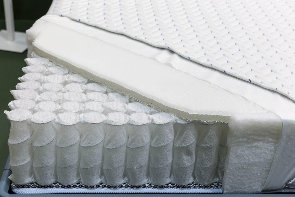 Aufgeschnittene Matratze zeigt Aufbau mit Sprungfedern und Schaumstoff