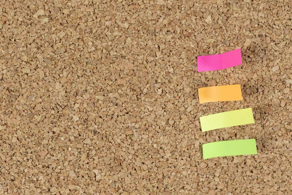 Aufkleber verschiedener Farben auf Tafel aus Kork