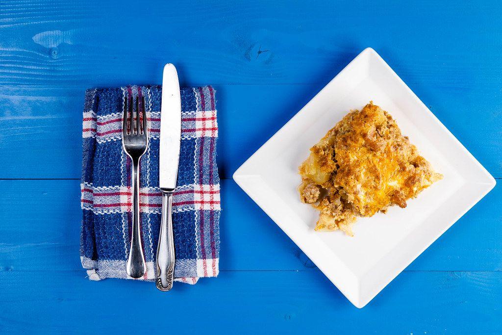 Auflauf mit Kartoffeln und Gehacktes auf weißem Teller neben Küchentuch und Besteck auf blauem Holztisch