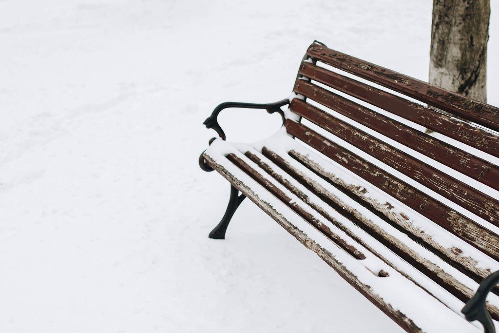 Aufnahme einer mit Schnee bedeckten Sitzbank. Winter