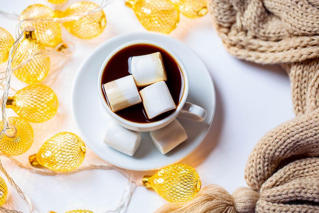Aufsicht auf eine Tasse heiße Schokolade mit Weihnachtslichtern auf weißem Hintergrund