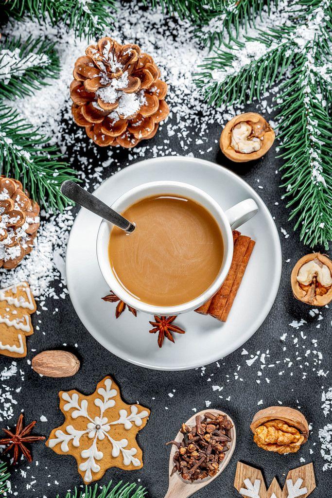 Aufsicht auf eine Tasse Kaffee mit Tannenzapfen und Zweigen, Nüssen und Plätzchen in Weihnachts-Fest-Dekor