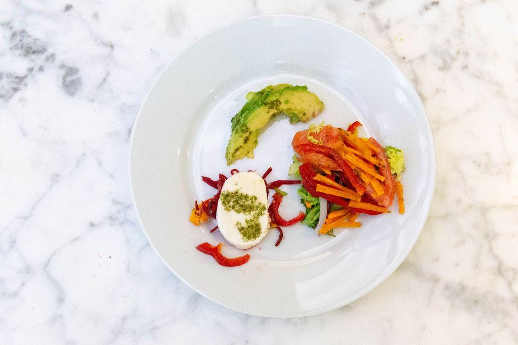 Aufsicht auf einen weißen Teller mit vegetarischer Gemüsespeiße mit Avocado und Mozzarella