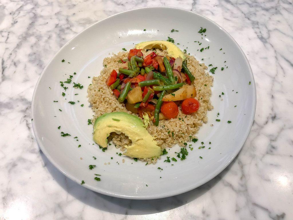 Aufsicht auf Quinoa Mahlzeit mit blanchiertem Gemüse mit Avocado un Petersilie auf einem weißem Teller