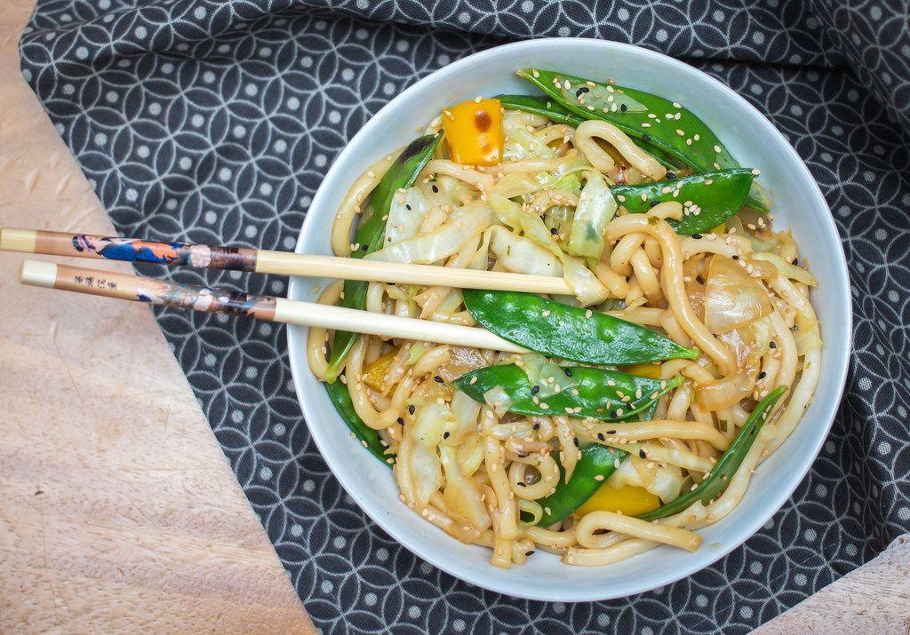 Aufsicht - Chow Mein Nudeln mit grünen Bohnen und Sesam in einer Schale mit Essstäbchen