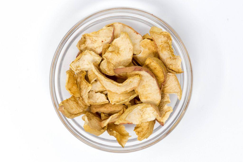 Aufsicht Dörrwerk - Getrocknete Apfel Chips mit Zimt in Glaschale auf weißem Hintergrund