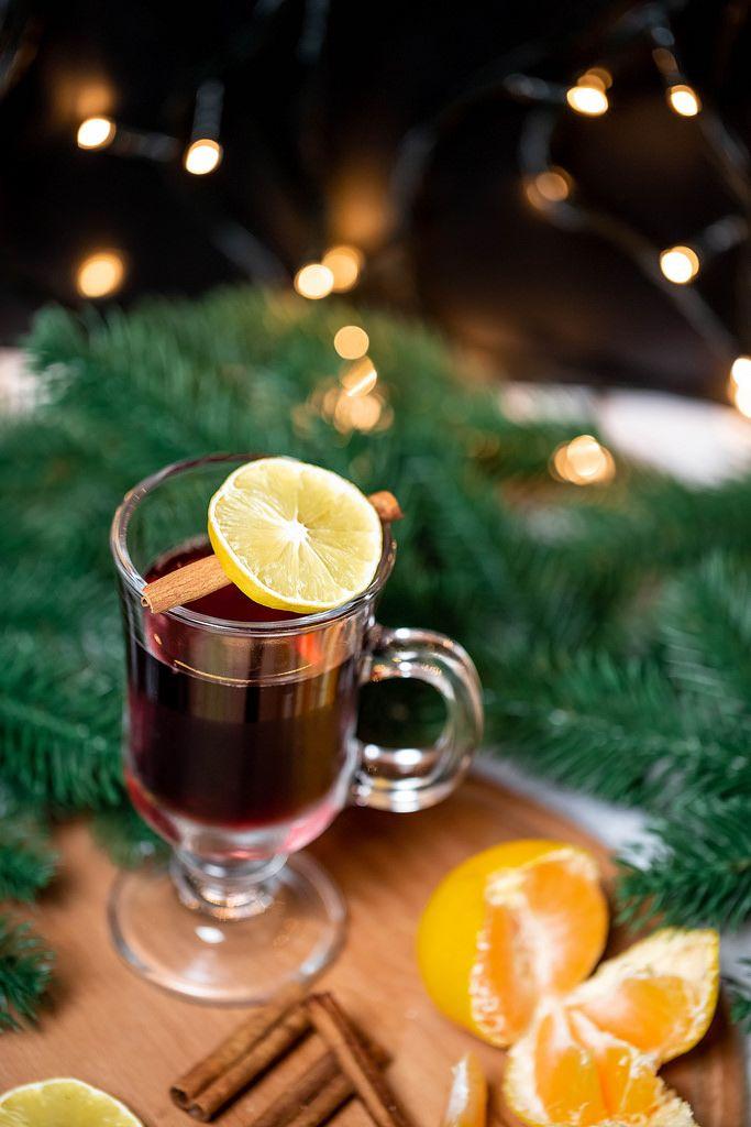 Aufsicht - Ein Glas Glühwein mit Zimtstange und einer Scheibe Zitrone  und Tannenzweigen im Hintergrund