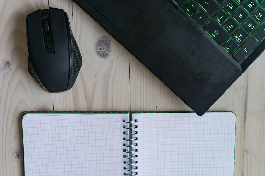 Aufsicht eines Laptops mit Maus und Notizheft