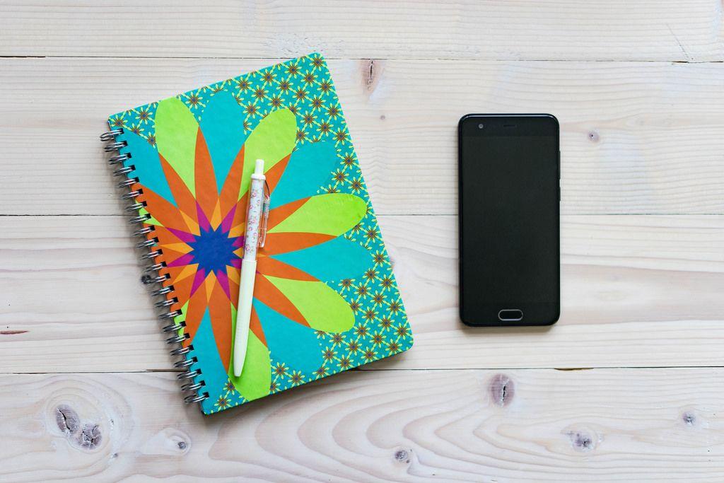 Aufsicht eines Notizhefts mit Stift und Smartphone auf Holztisch