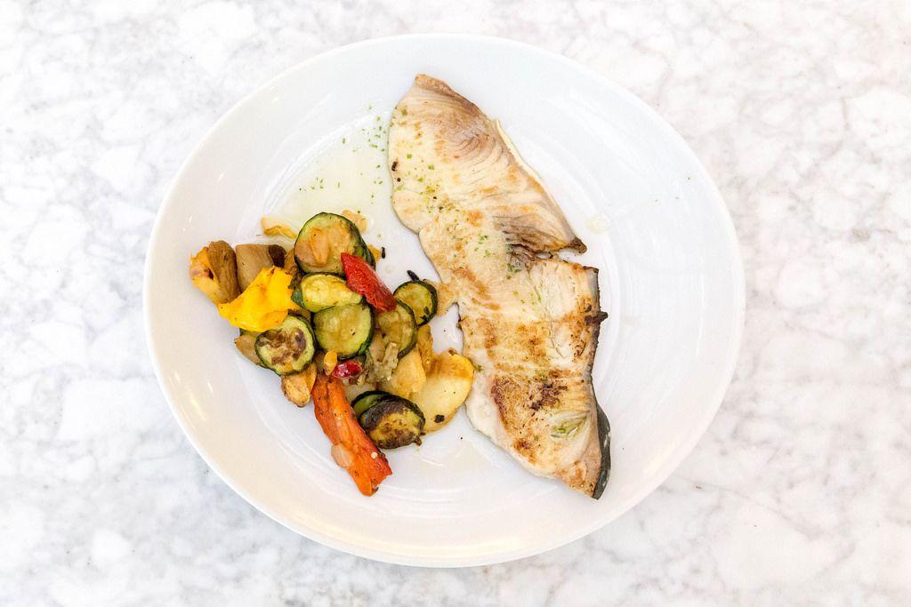 Aufsicht - Gegrillter Schwertfisch mit Gemüse auf einem weißen Teller auf Marmor-Untergrund